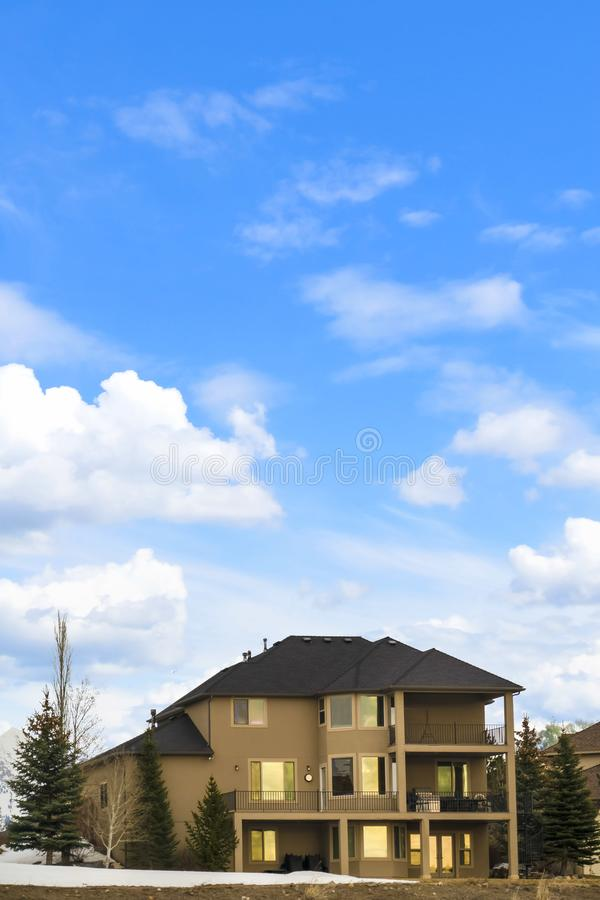Three storey home with porch and balcony against blue sky with bright clouds. Coniferous trees and snow covered ground can be seen outside the house royalty free stock image