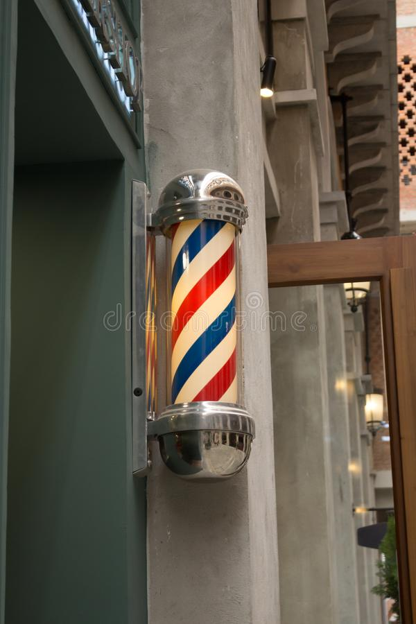 Three Striped Blue White Red Vintage Barber Pole Sign With Yellow Light Inside. Sideview of vintage barber pole sign in front of barbershop near ChiangMai at royalty free stock photography