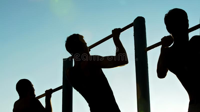 Three strong sportsmen doing actively pull-ups on chin-up bars outdoors, sport. Stock photo stock photo
