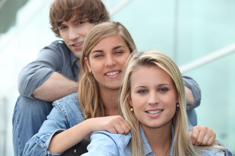 Three students. Sitting in line royalty free stock photos