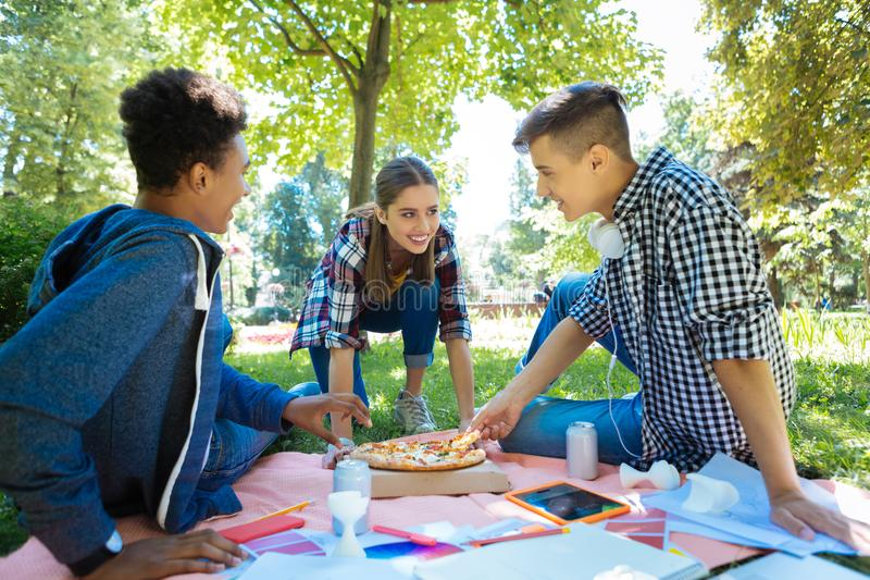 Three students eating pizza while having picnic in nature stock photo