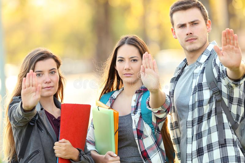 Three students gesturing stop in a park. Three angry students gesturing stop in a park royalty free stock photo