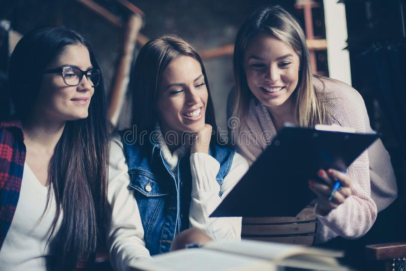 Three students girl reading file together indoors. stock photos