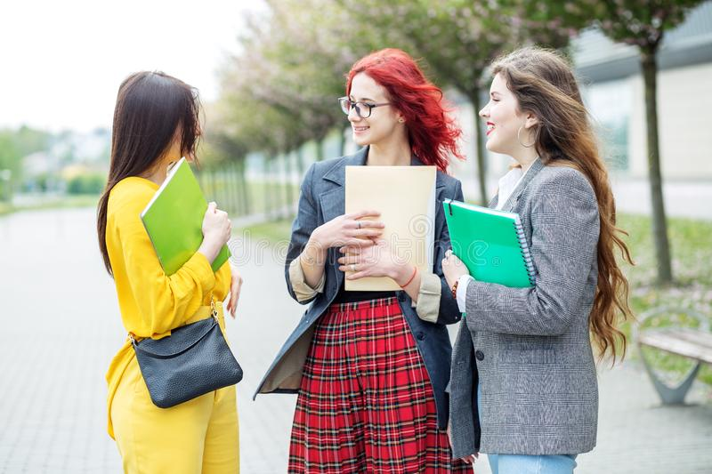 Three students are talking about their studies on the campus. Education concept, friendship and group of people royalty free stock image