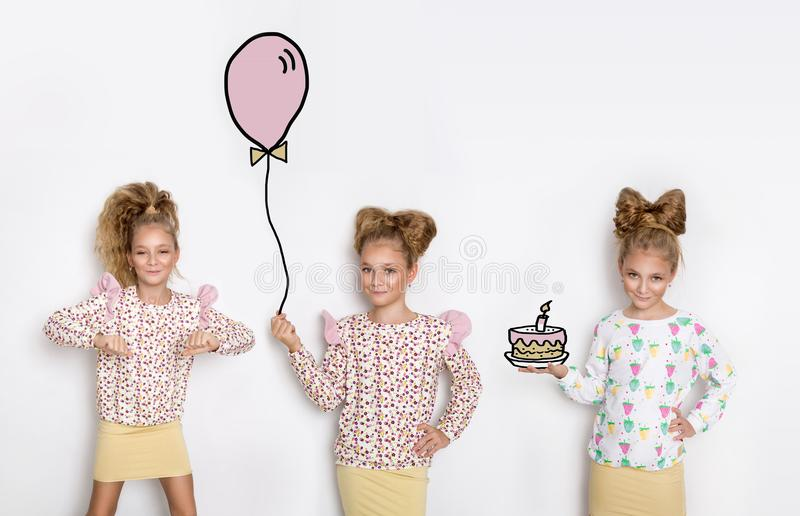 Three stunning beautiful little girls with long blond hair standing on a white background and one of them holds a balloon, the sec stock images