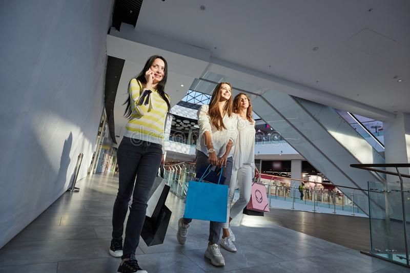 Three stylish girls dressed in nice casual clothes walk with lots of shopping bags in the modern mall. Shopping time stock photography