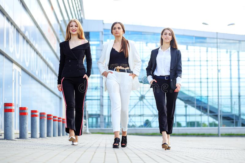Three successful women left the office. Concept for business, boss, robot, team and success stock photography