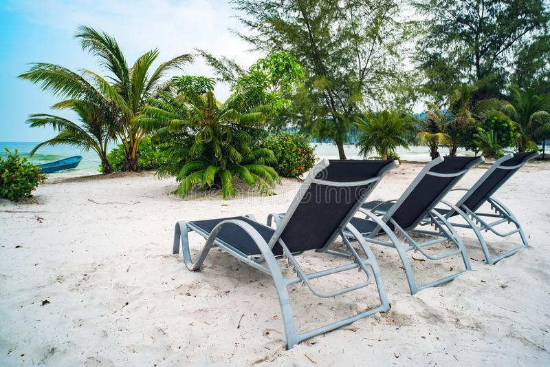 three sun loungers stand on the white sand against the blue sky and the clear sea with turquoise water. The concept of recreation stock photography