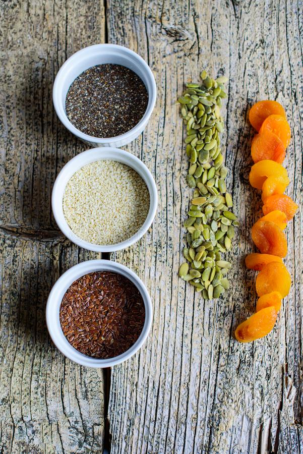 Three super foods chia, flax and sesame seeds in white pals on a wooden background, and next to the seeds of pumpkin and dried apr. Icots. Top view stock photos