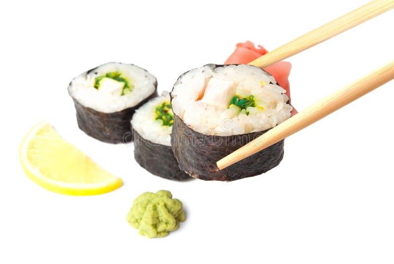 Three sushi, wasabi, gringer, lemon and sticks
