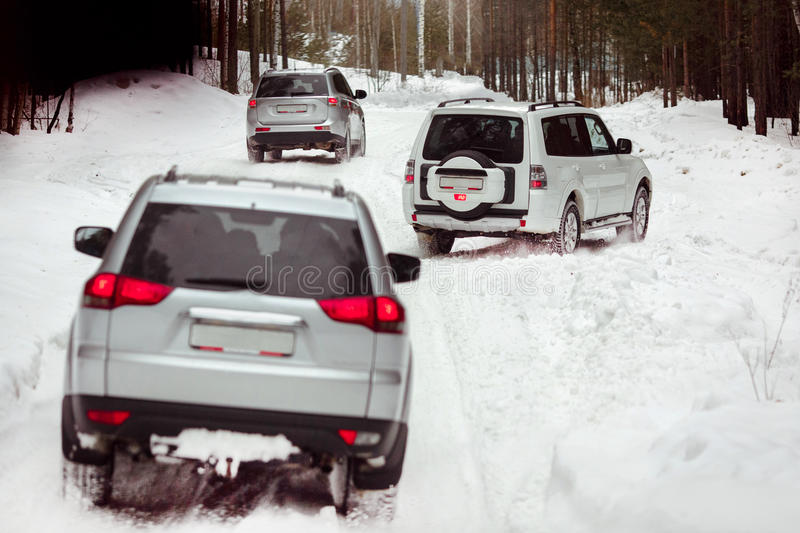 Three SUVs in the woods in winter in the rally royalty free stock photos