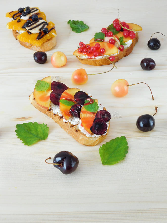Three sweet bruschettas with berries, fruits and cream cheese stock images