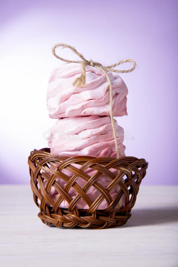 Three sweet pink cakes in a wooden basket. Pink cherry marshmallows stock photography