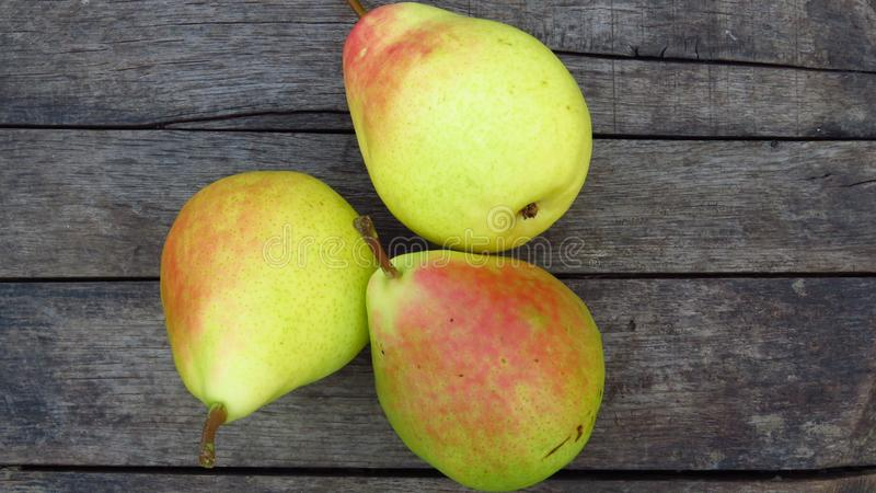 Three Organic Yellow Pear Fruits. Natural Pear Harvest on Wood Texture Background. stock images