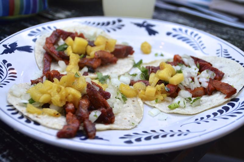 Three tacos al pastor on corn tortillas. Fresh tacos al pastor, popular and traditional Mexican street food consisting of pork tacos on corn tortillas with royalty free stock images