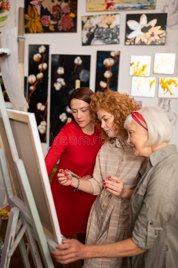 Three talented beautiful women painting on canvas together royalty free stock photography