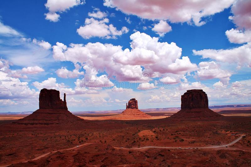 Butte rock formations with dirt road, shadows and fluffy clouds in Monument Valley, Arizona. Three tall butte rock formations are visible across an open desert royalty free stock photo