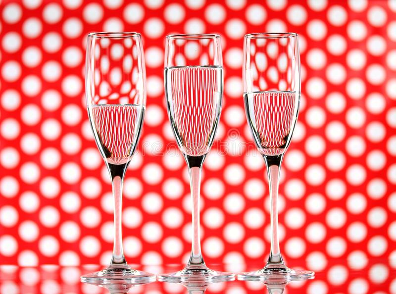 Three glasses of water on a red circle background showing refraction. Canvas wall art royalty free stock photo