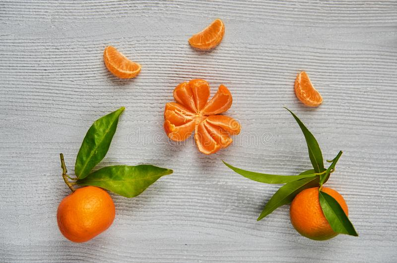 Three tangerine orange slices on the gray wooden board with free copy space. Two fresh raw mandarins orange with green leaves royalty free stock photo