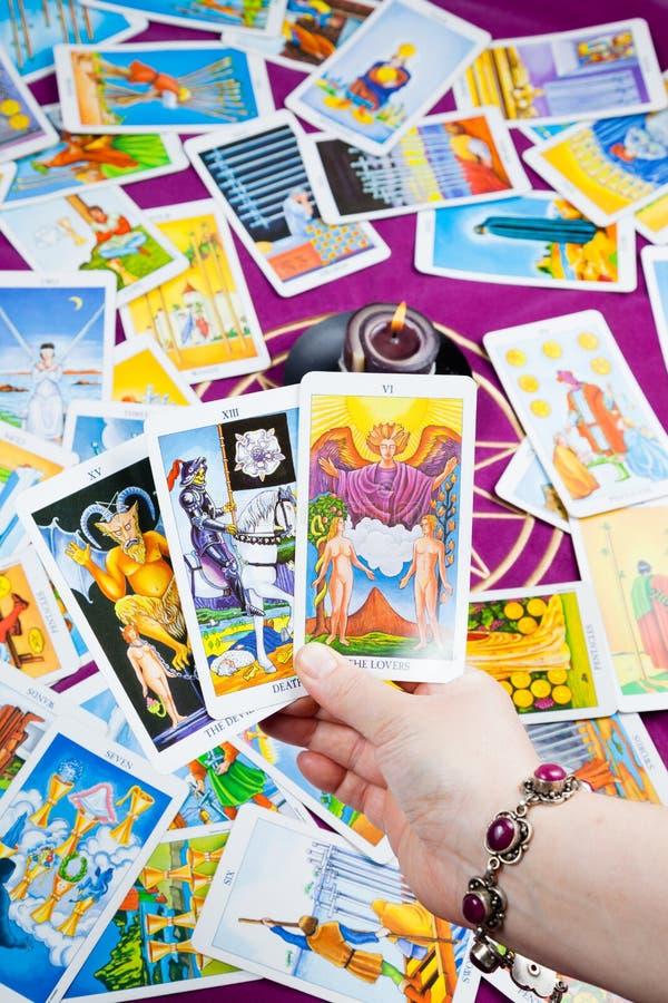 Three tarot cards held in hand. stock photography