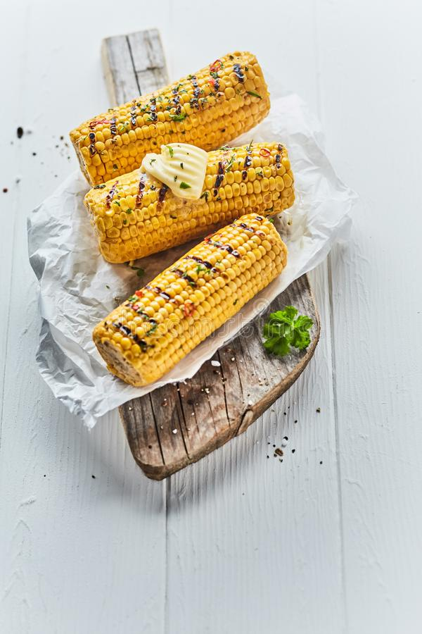 Three tasty grilled corn on the cob stock images