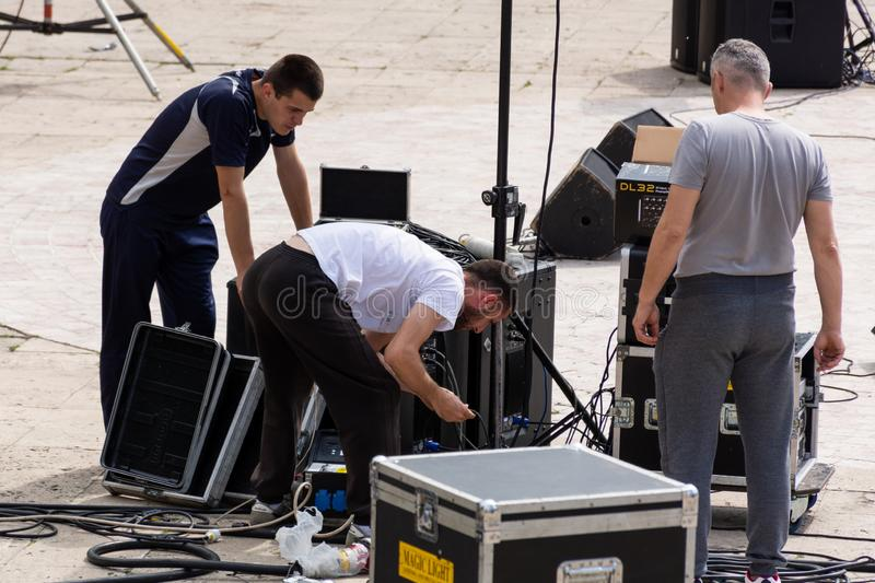 Three technicians connect the music cables and the speakers outside stock photos