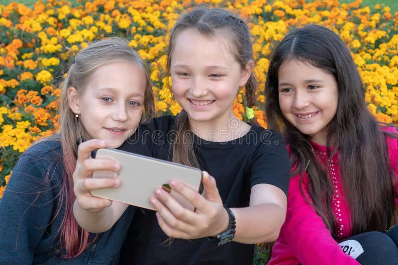 Three teen girls take a selfie on Phone  on a sunny day and laugh. stock images