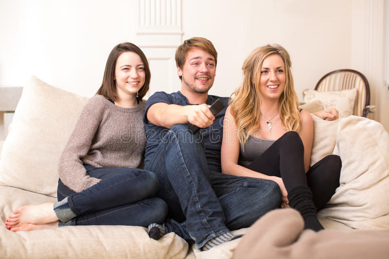 Three teenage friends sitting watching television stock images