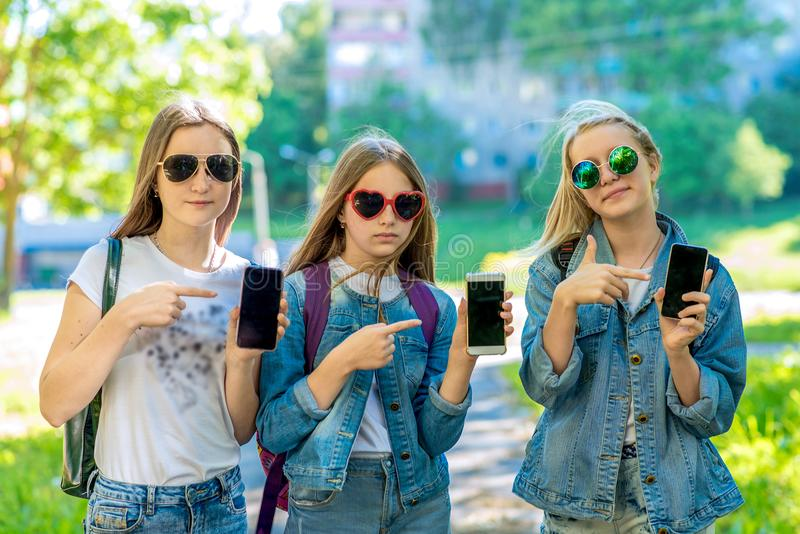 Three teenage girls. Summer in nature. In his hands holds a smartphone. Sunglasses. In denim suits. A gesture of hands royalty free stock photography