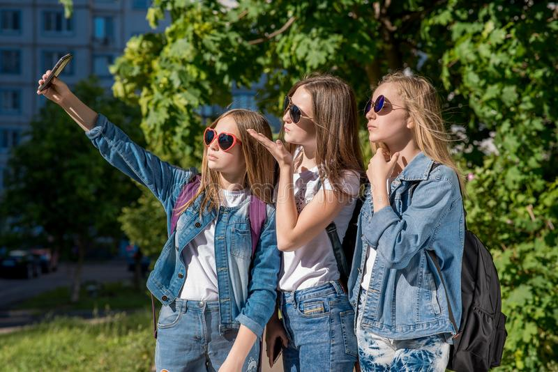 Three teenage girls in summer outdoors. Makes a photo of the person on phone. They wear stylish jeans clothes. Sunny royalty free stock photo
