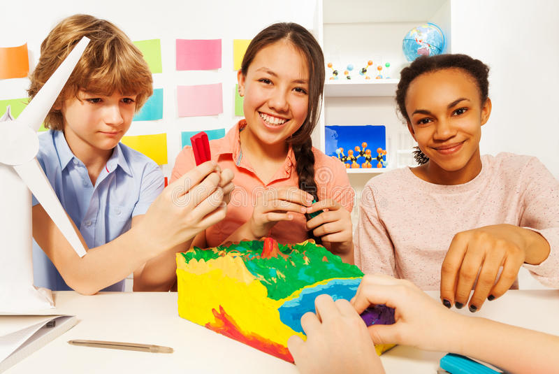 Three teenage kids modeling topographical relief. Three teenage kids creating topographical relief with modeling clay at the classroom stock photos