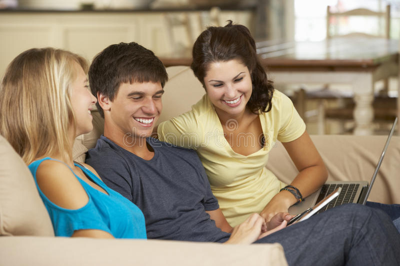 Three Teenagers Sitting On Sofa At Home Using Mobile Phone, Tablet Computer And Laptop stock images