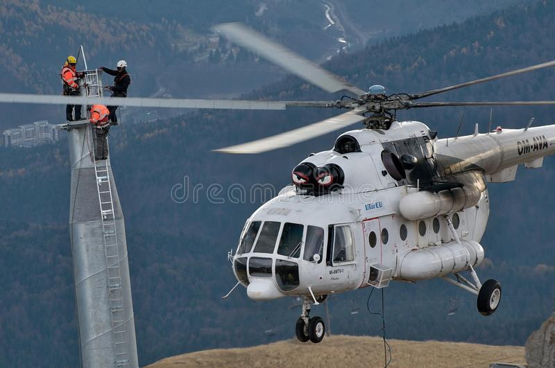 Three thumping assemblers under the helicopter royalty free stock image