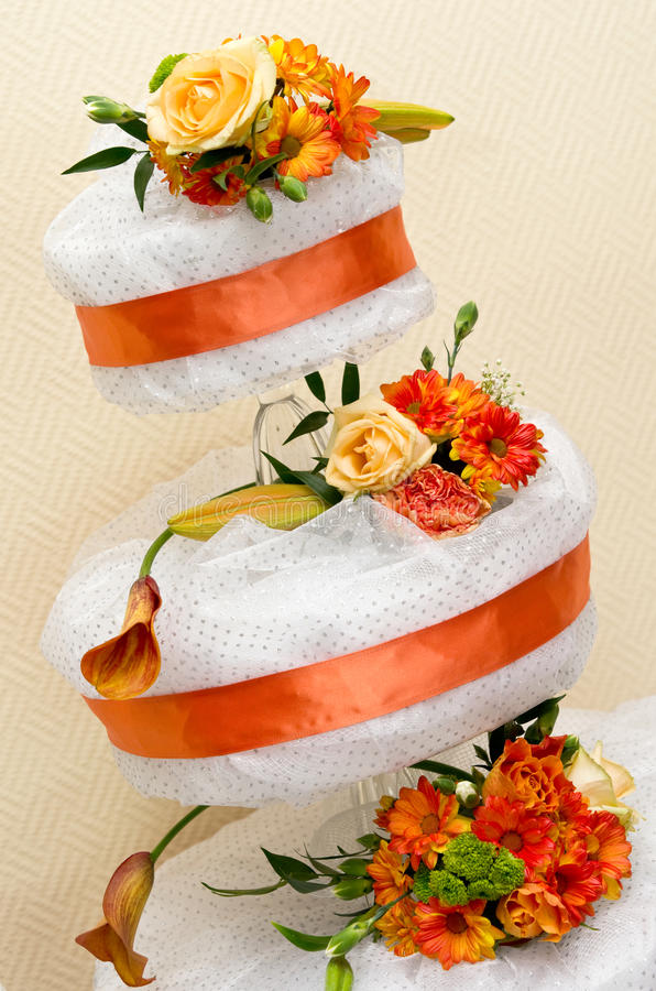 Three tier wedding cake. Closeup of three tier wedding cake with flowers and orange ribbons stock photos