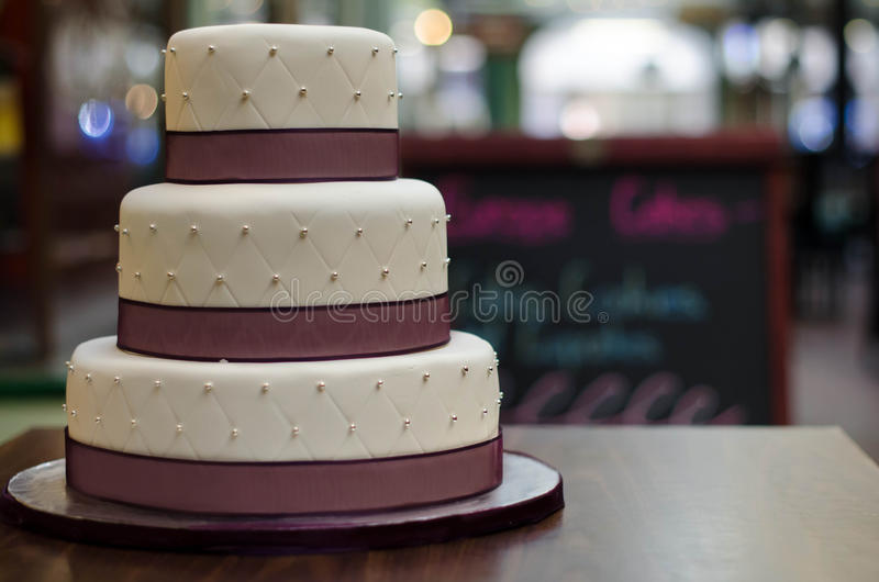 Three tier white burgundy wedding cake with pattern and silver pearls stock photo