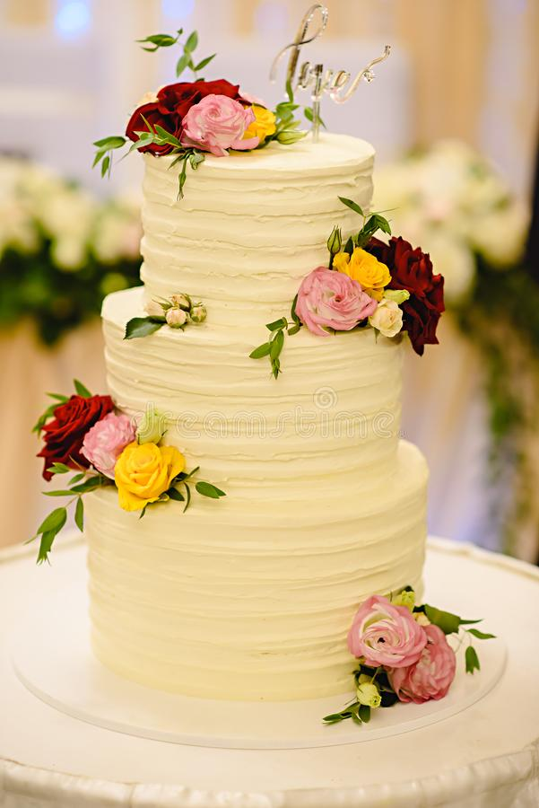 Three-tiered white wedding cake decorated with flowers from mastic on a white wooden table. stock images