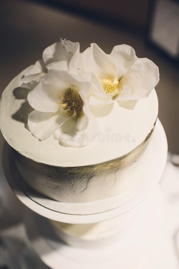 Three-tiered white wedding cake decorated with flowers from mastic on a white wooden table. Picture for a menu or a stock photography