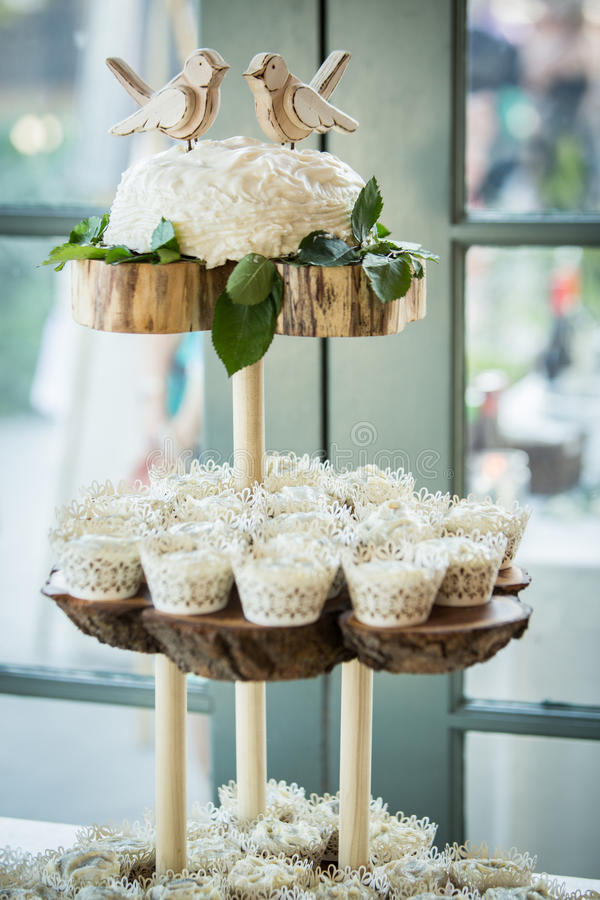 A three tiered wooden display with cupcakes. A three tiered wooden display at a wedding featuring cupcakes, wooden birds, and details of leaves stock photos