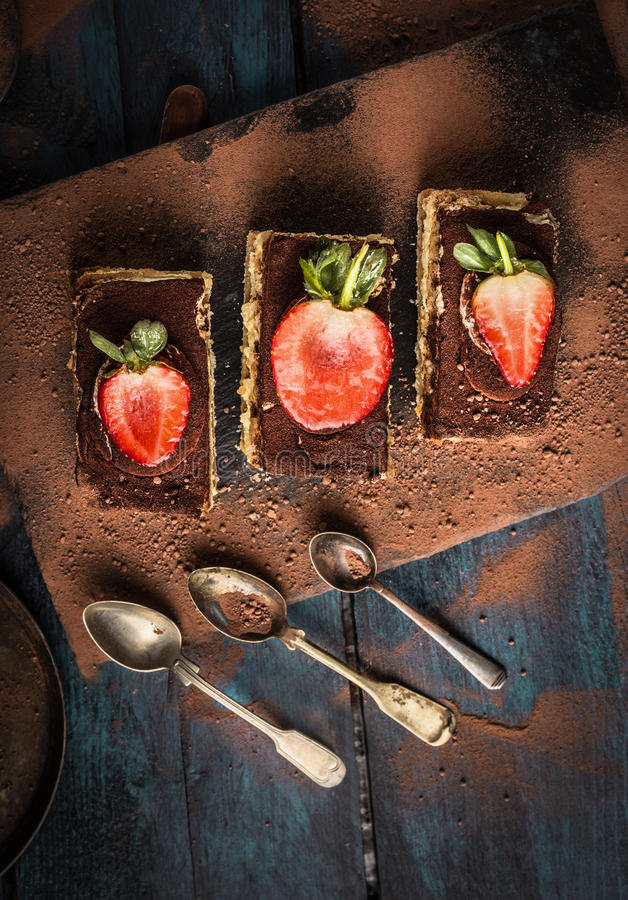 Three tiramisu cake with strawberries and spoons on dark blue wooden royalty free stock image
