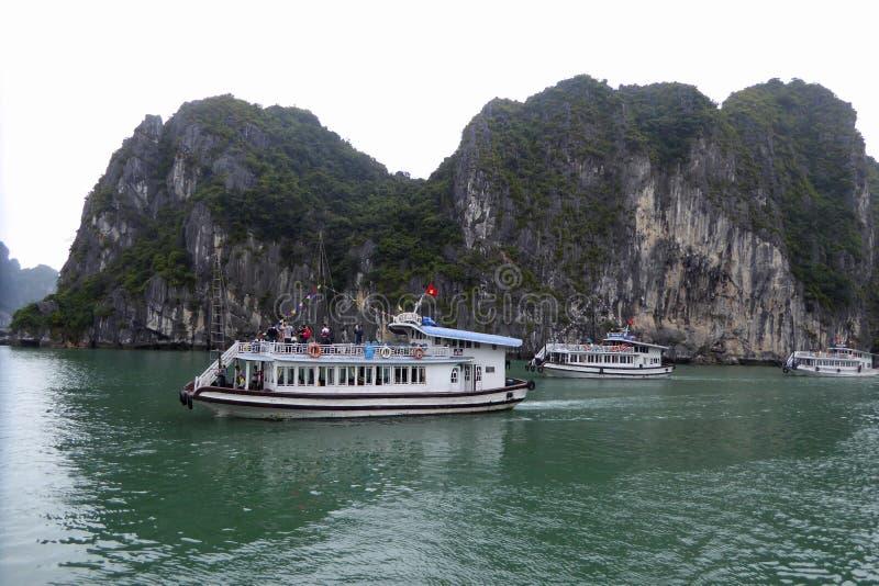 Three tourists boats near the islands of ha long bay Vietnam royalty free stock image