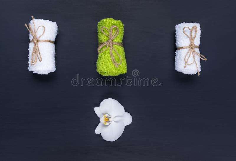 Three towels for spa rolled up on a roll lie on a black background stock image