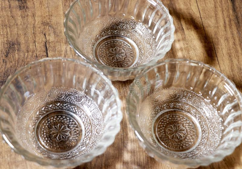 Three transparent empty salad bowls on wooden table royalty free stock photography