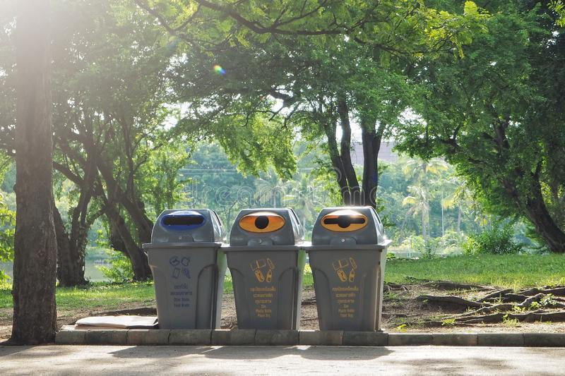 Three trash in the garden. Each bin is separated type of waste. Each trash including icon, Thai and English for specific waste. stock photos