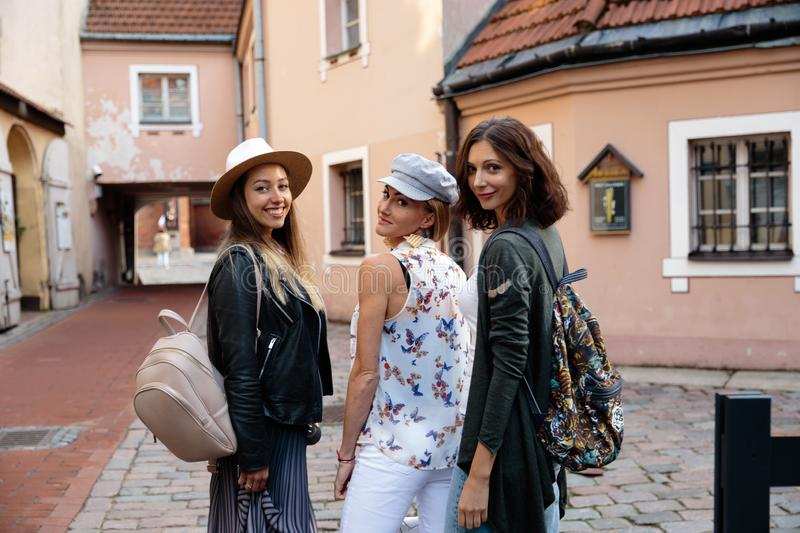 Three traveling girl friends with light backpacks walking exploring Riga city - Travel tourism concept after transfer stock photography