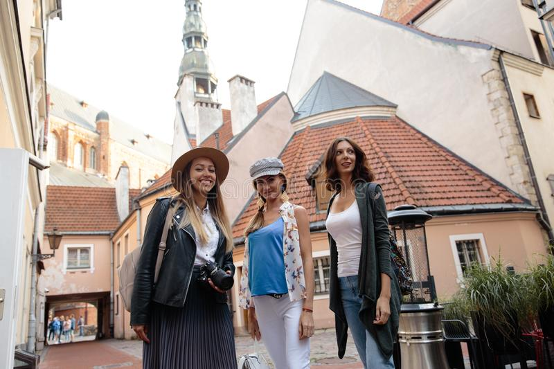 Three traveling girl friends with light backpacks walking exploring Riga city - Travel tourism concept after transfer royalty free stock photo