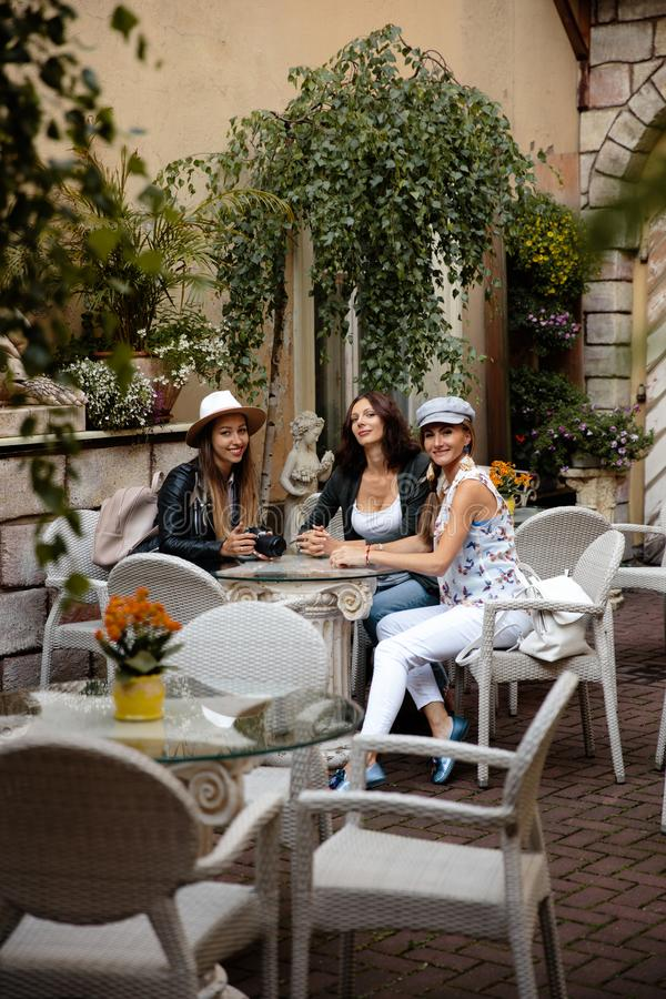 Three traveling girl friends sitting in italian restaurant with light backpacks exploring Riga city - Travel tourism royalty free stock image