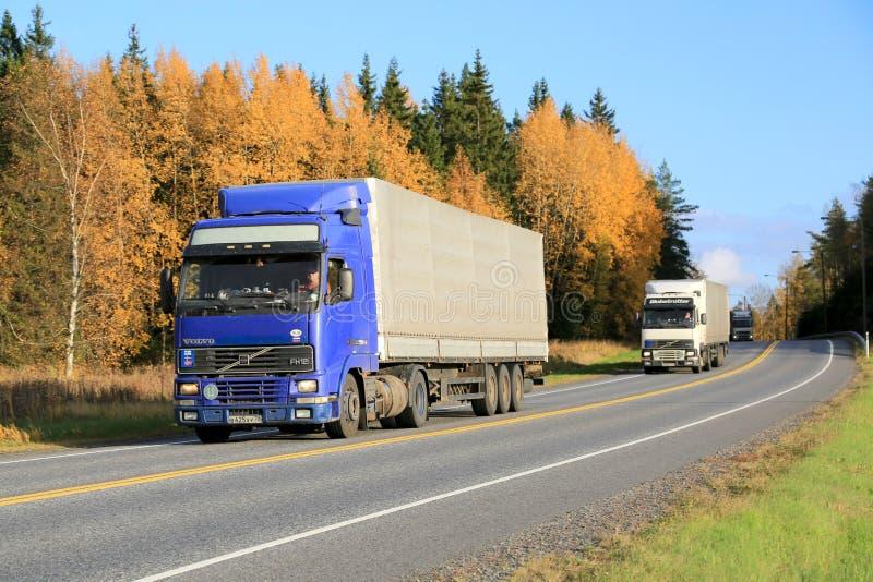 Three Trucks Platooning on a Highway in Autumn. KAARINA, FINLAND - OCTOBER 4, 2014: Three Volvo FH12 trucks are driven in a platoon. The advantages of platooning
