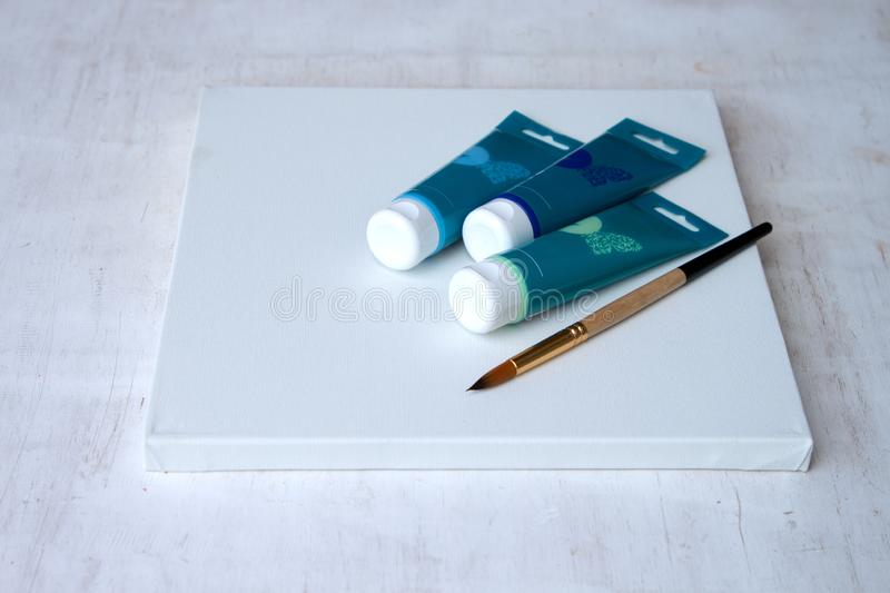 Three tubes of acrylic paint and a brush on white canvas. The set of the artist. stock images