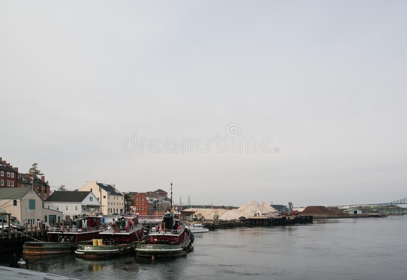 Three tugboats in a harbor stock images