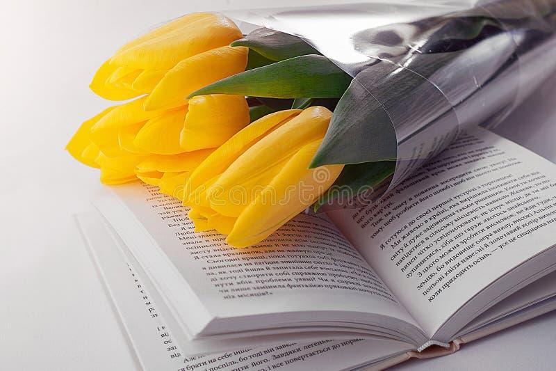 Three tulips on open book royalty free stock photos